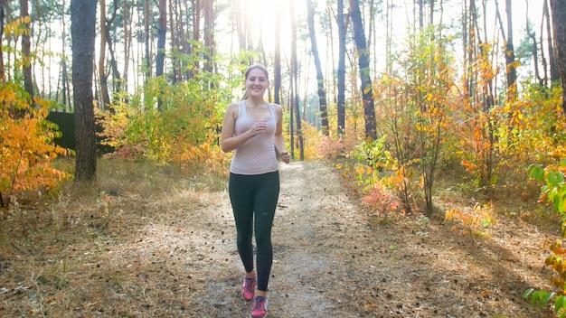 Heureuse femme souriante en leggings courant en forêt par une journée ensoleillée.