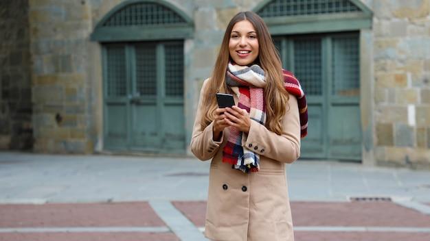 Heureuse femme souriante avec manteau et écharpe à l'aide de téléphone intelligent dans la rue de la ville, regardant la caméra. copiez l'espace.