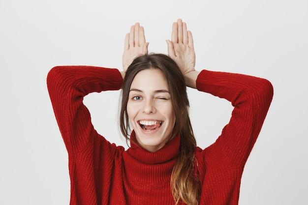 Heureuse femme souriante montre des oreilles de lapin derrière la tête