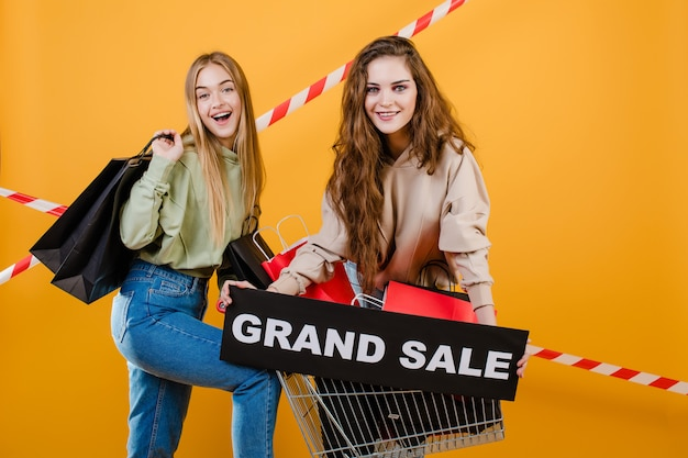 Heureuse femme souriante ont signe de grande vente avec panier rempli de sacs à provisions et de ruban de signalisation isolé sur jaune