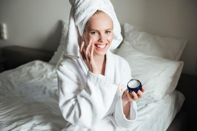 Heureuse femme souriante en peignoir mettant la crème sur le visage