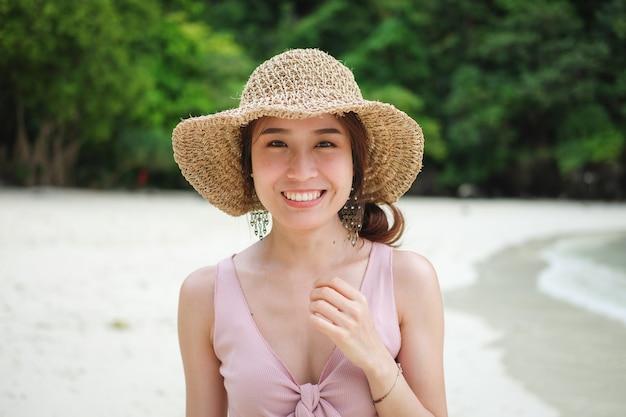 Heureuse femme souriante sur la plage en été.
