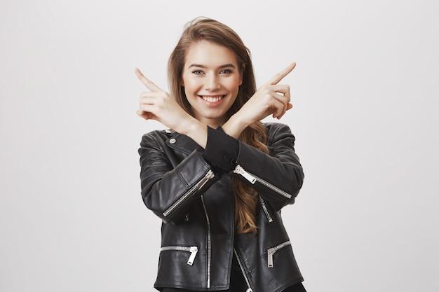Heureuse femme souriante pointant sur le côté avec les mains croisées sur le corps