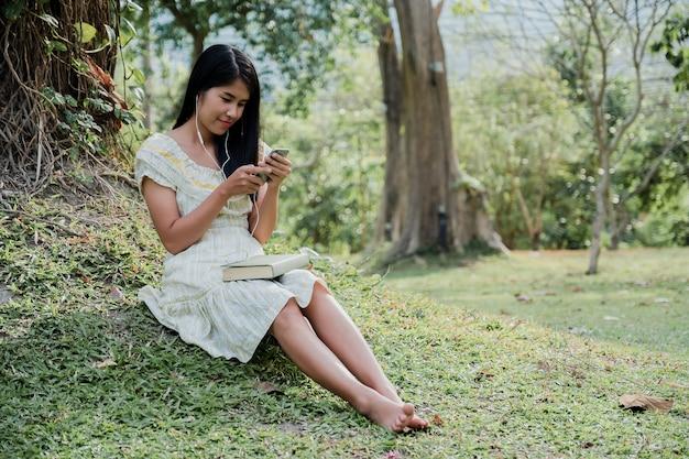 Heureuse femme souriante portant des écouteurs assis sur le parc en écoutant de la musique sur un smartphone