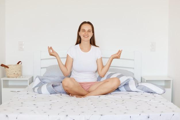 Heureuse femme souriante portant un t-shirt et un short de style décontracté blanc, assise sur le lit dans une chambre lumineuse, méditant à la maison le matin, exprimant des émotions positives.