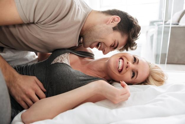 Heureuse femme souriante en position couchée et jouant avec son mari