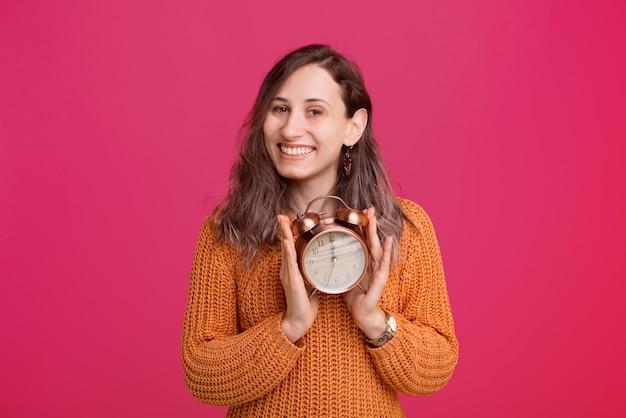 Heureuse femme souriante en pull tenant un réveil