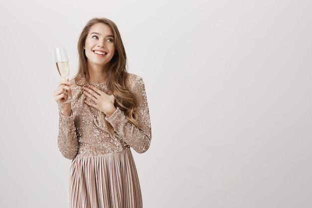 Heureuse femme souriante en robe de soirée, boire du champagne