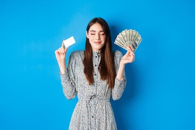 Heureuse femme souriante à la satisfaction des yeux fermés, montrant des billets d'un dollar et une carte de crédit en plastique, debout rêveur contre le bleu.