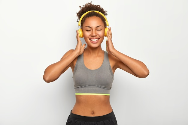 Heureuse femme souriante se détend après avoir fait des exercices, porte des vêtements sportifs, écoute de la musique via des écouteurs modernes, a la bonne humeur