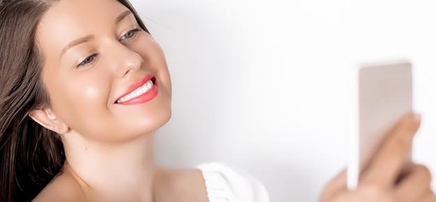 Heureuse femme souriante avec un smartphone ayant un appel vidéo ou prenant un portrait de selfie sur fond blanc concept de technologie et de communication des gens