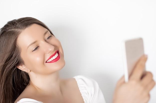 Heureuse femme souriante avec un smartphone ayant un appel vidéo ou prenant un selfie portrait sur fond blanc concept de technologie et de communication des gens