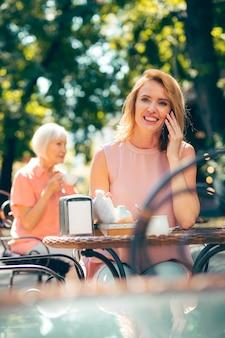 Heureuse femme souriante à la table du café à l'extérieur, profitant d'une agréable conversation téléphonique