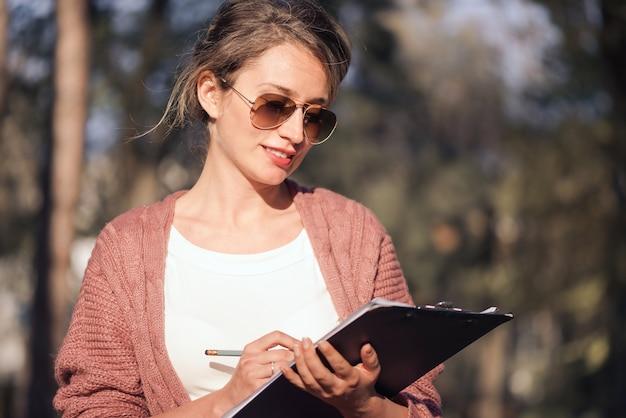 Heureuse femme souriante travaillant avec des papiers et écrivant des lettres