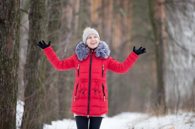 Heureuse femme souriante en veste d'hiver rouge, en plein air