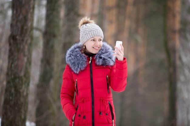 Heureuse femme souriante en veste d'hiver rouge regarde sur son téléphone mobile, en plein air
