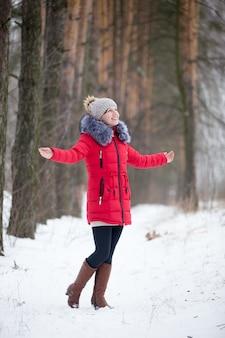 Heureuse femme souriante en veste d'hiver rouge réjouissant à l'extérieur