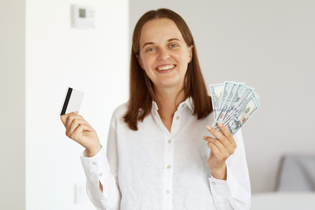 Heureuse femme souriante vêtue d'une chemise blanche de style décontracté, tenant un grand fan de billets de banque et de carte de crédit, banque, remboursement, économiser de l'argent, posant dans une pièce lumineuse à la maison.