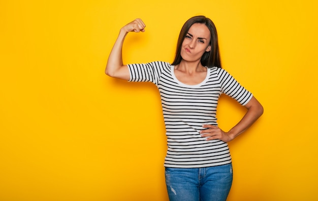 Heureuse femme sportive belle et forte montre ses biceps isolés sur fond jaune
