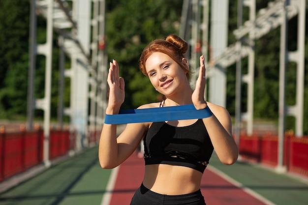 Heureuse femme sportive faisant de l'exercice avec les mains avec une bande de résistance en caoutchouc