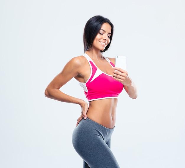Heureuse femme sportive faisant photo sur smartphone