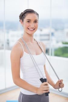 Heureuse femme sportive tenant une corde à sauter