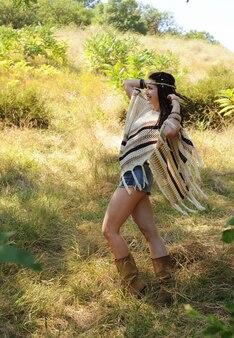 Heureuse femme de style bohème vêtue d'un poncho tricoté, d'un short en jean et d'un bandeau posant les mains contre le parc ensoleillé d'automne
