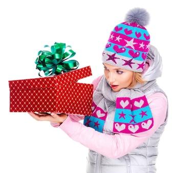 Heureuse femme surprise avec un cadeau de noël dans un vêtement d'hiver isolé sur blanc