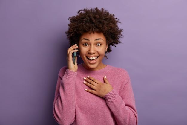 Heureuse femme surprise se sent touchée de recevoir les félicitations d'un vieil ami, bénéficie d'appels gratuits en itinérance, rit pendant les conversations sur smartphone, garde la main sur la poitrine