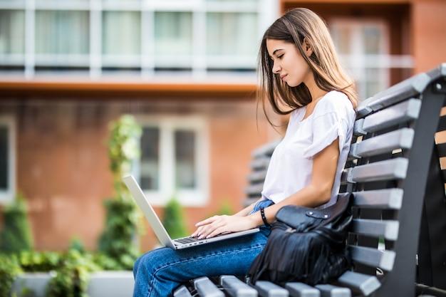 Heureuse femme tapant sur un ordinateur portable et regardant la caméra assise sur un banc à l'extérieur