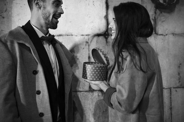 Heureuse femme tenant une boîte présente près d'un jeune homme