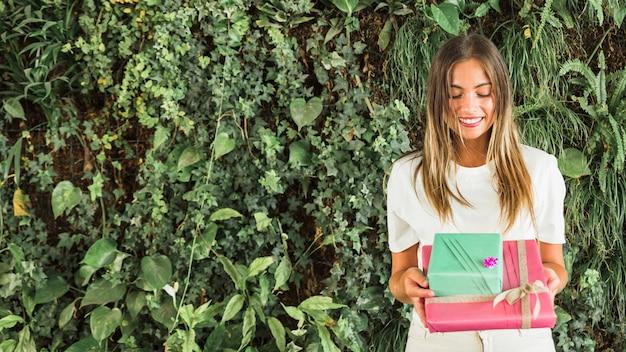 Heureuse femme tenant des boîtes-cadeaux devant des feuilles vertes
