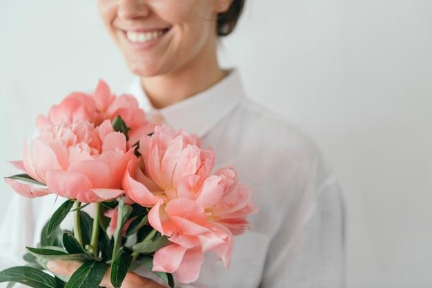 Heureuse femme tenant un bouquet de pivoines