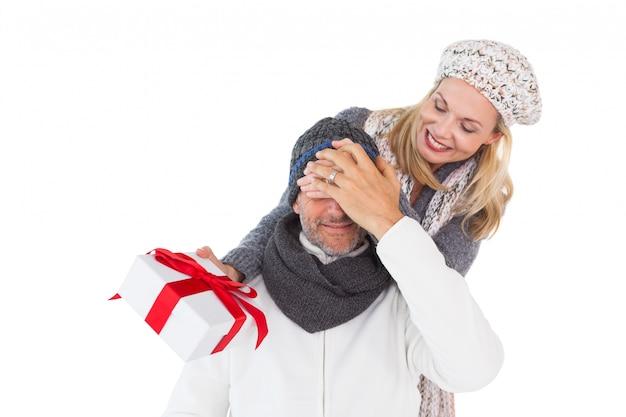 Heureuse femme tenant un cadeau tout en couvrant les yeux des maris