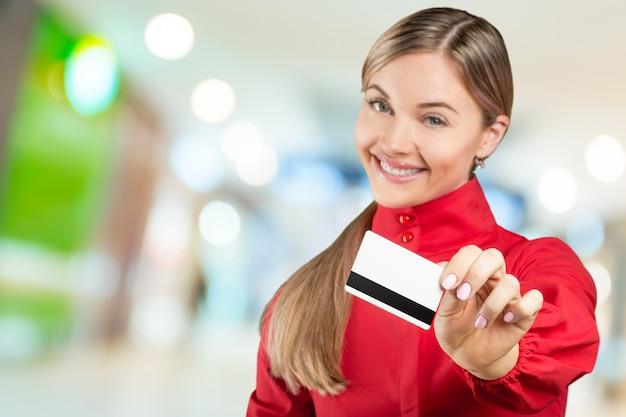 Heureuse femme tenant une carte de crédit. concept commercial