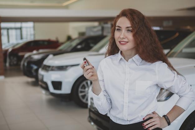 Heureuse femme tenant des clés de voiture à sa nouvelle automobile