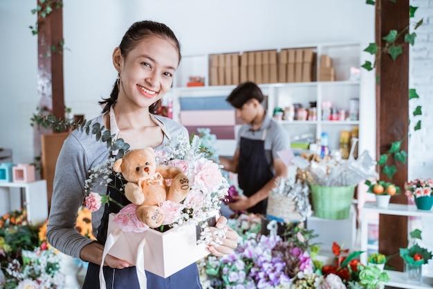 Heureuse femme tenant un emballage cadeau prêt à vendre. travaillant dans une boutique de fleuriste portant un tablier debout avec un ami