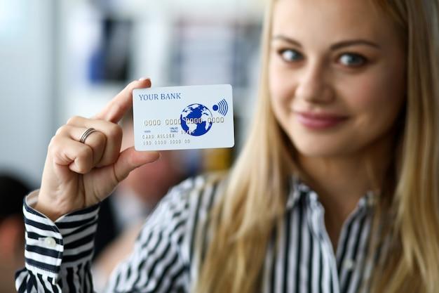 Heureuse femme tenant à la main une carte en plastique en relief
