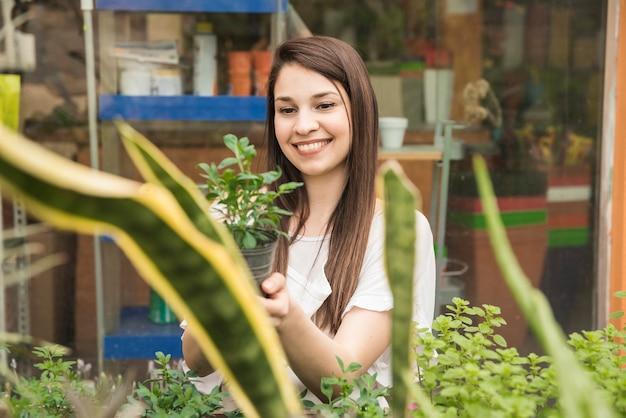 Heureuse femme tenant des plantes en pot en serre