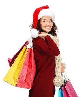 Heureuse femme tenant des sacs à provisions sur une surface blanche. concept de magasinage de noël