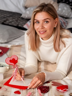 Heureuse femme tenant un stylo coeur