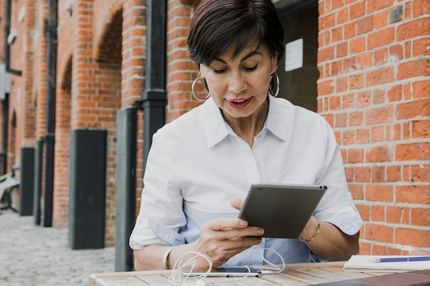 Heureuse femme tenant une tablette à l'extérieur