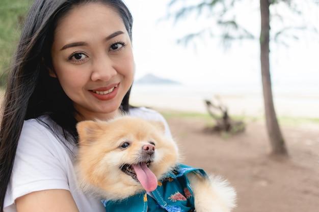 Heureuse femme tient un chien poméranien. concept de meilleur ami humain.