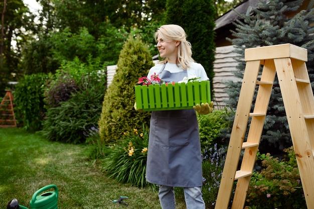 Heureuse femme tient un lit de fleur dans le jardin