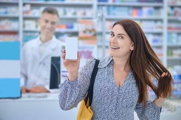 Heureuse femme touchant les cheveux debout en pharmacie