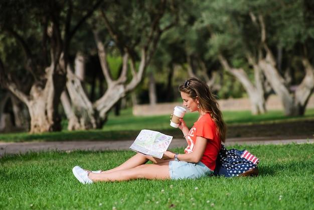 Heureuse femme touriste relaxant dans le parc