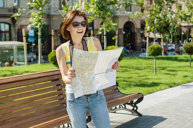 Heureuse femme touriste tenant une caméra et une carte