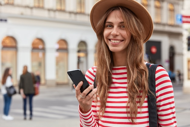 Heureuse femme touriste utilise les informations du blog de voyage, détient un smartphone, se promène dans la rue de la ville, porte un chapeau élégant et un pull rayé