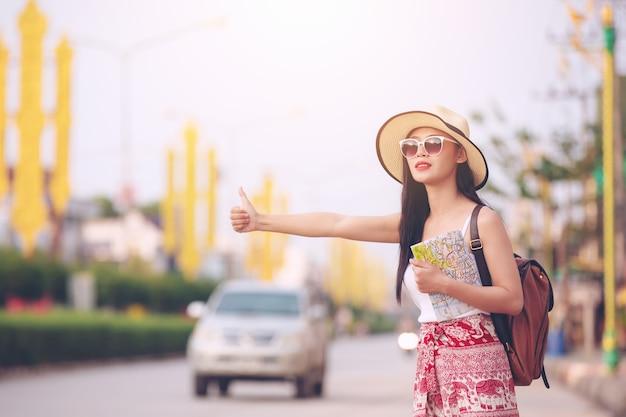 Heureuse femme touristique à agiter le bus pendant les vacances, concept de voyage.