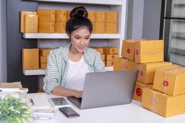 Heureuse femme travaillant avec un ordinateur portable et une boîte à lettres de courrier au bureau à la maison
